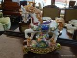 ROCKING PORCELAIN HORSE; IS GOLD, PURPLE, BROWN, AND WHITE IN COLOR. MEASURES 13 IN X 13 IN