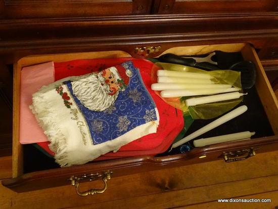 (DR) CONTENTS OF LOWER PORTION OF CHINA CABINET; CHRISTMAS TOWELS, CANDLES, CHRISTMAS PLACEMATS,