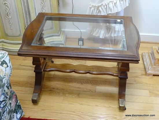 (LR) COFFEE TABLE; REGENCY STYLE WALNUT BEVELED GLASS COFFEE TABLE RESTING ON BRASS CASTERS- 26 IN X