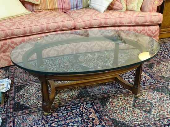 (LR) COFFEE TABLE- OVAL WALNUT AND GLASS TOP TABLE WITH STRETCHER BASE- 45 IN X 30 IN X 16.5 IN