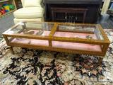 WOODEN DISPLAY CASE OTTOMAN; MAPLE OTTOMAN WITH PANELED GLASS DISPLAY WINDOWS. THE TWO SMALLER SIDE