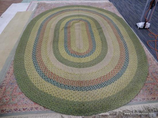 BRAIDED RUG; OVAL SHAPED BRAIDED RUG IN HUES OF GREEN, YELLOW, RED, AND BLUE. MEASURES 8 FT 7 IN X