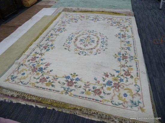 hand knotted area rug; cream colored floral rug with pink, yellow and blue flowers. has fringe