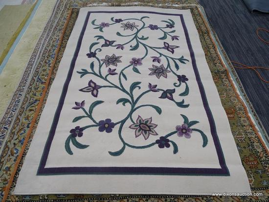 MACHINE MADE AREA RUG; CREAM COLORED RUG WITH PURPLE, GREEN, AND TAN FLOWERS ON IT. MEASURES 5 FT 1