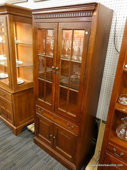 (R1) WOODEN DISPLAY CABINET; CABINET WITH DENTAL MOLDING SITTING ABOVE 2 GLASS PANELED CABINET DOORS
