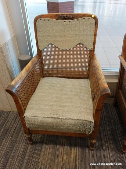 (DOOR) WICKER ARMCHAIR; WOODEN ARMCHAIR WITH A WICKER LACED BACK AND SIDES. HAS A FADED BLUE FABRIC,
