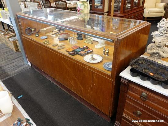 (R1) DISPLAY CASE; WOODEN DISPLAY CASE WITH GLASS ON THE TOP AND THE FRONT, 4 SLIDING DOORS ON THE