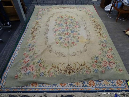 WOVEN AREA RUG; HAS A BEIGE AND GREEN COLOR BASE WITH PINK AND BLUE FLOWERS. HAS BROWN COLORED