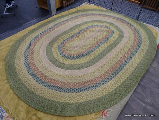 OVAL RUG; HAS A MULTI COLORED, ROPE LIKE RING DESIGN TO INCLUDE MULTIPLE TONES OF GREEN, YELLOW,