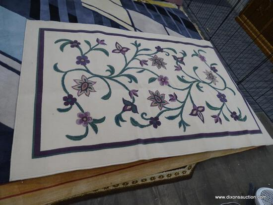 FLOWER AREA RUG; CREAM, PURPLE, AND GREEN AREA RUG WITH A VIOLET FLORAL DESIGN. MEASURES 5 FT X 8