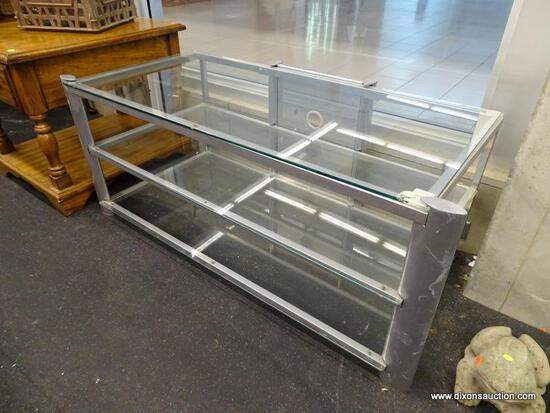 (WINDOW) TV STAND; THREE TIERED GLASS TOP MODERN TV STAND. HAS A SILVER FRAME. MEASURES 50 IN X 23.5