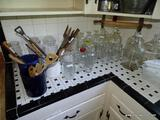 (KITCHEN) LOT OF ASSORTED GLASSWARE; COUNTER LOT TO INCLUDE 5 VINEGAR JARS, 5 MILK BOTTLES, 15