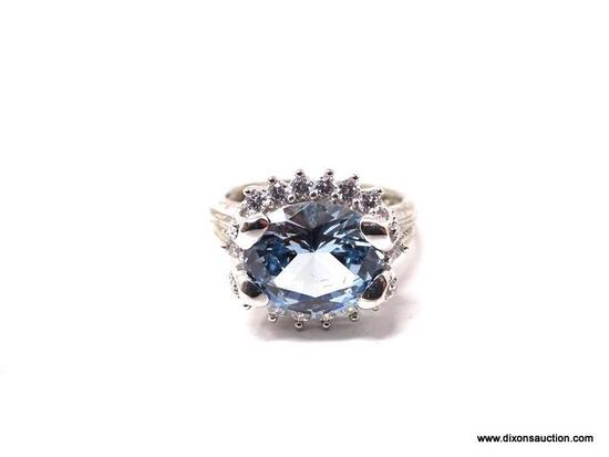 .925 STERLING SILVER RING WITH LARGE CENTER AQUAMARINE SURROUNDED BY SMALL CZ GEMSTONES. MADE BY