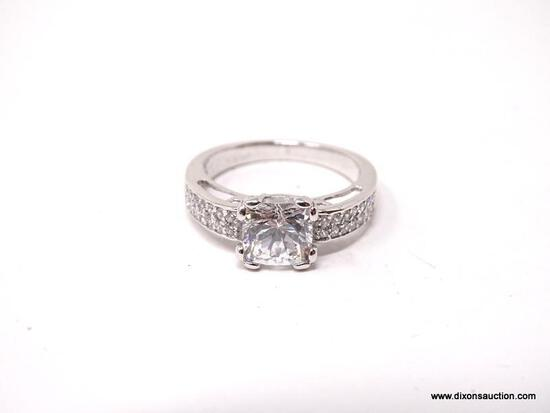 .925 STERLING SILVER RING WITH LARGE PRINCESS CUT CZ ACCOMPANIED BY SMALLER CZ STONES ON EACH SIDE.