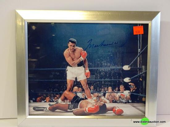 MUHAMMAD ALI PHOTOGRAPH; SHOWS ALI TOWERING OVER A DEFEATED OPPONENT. IS SIGNED AND HAS COA ON THE