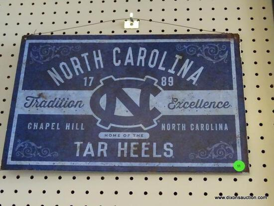 """TAR HEELS ADVERTISING SIGN; IS BLUE AND LIGHT BLUE IN COLOR WITH THE WORDS """"NORTH CAROLINA TAR"""