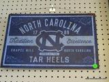 TAR HEELS ADVERTISING SIGN; IS BLUE AND LIGHT BLUE IN COLOR WITH THE WORDS
