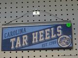 CAROLINA TAR HEELS ADVERTISING SIGN; IS BLUE AND LIGHT BLUE IN COLOR. MEASURES 12 IN X 5.5 IN
