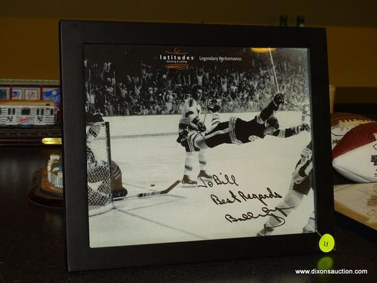 (BAS) FRAMED AND AUTOGRAPHED PHOTO OF BOBBY ORR FROM LATITUDES DECK & RAILING. IS IN A BLACK FRAME
