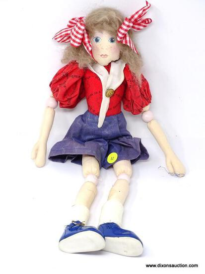CLOTH DOLL IN THE FORM OF A GIRL WITH PLAID RED RIBBONS IN HER HAIR, A RED SHIRT, AND A BLUE SKIRT.