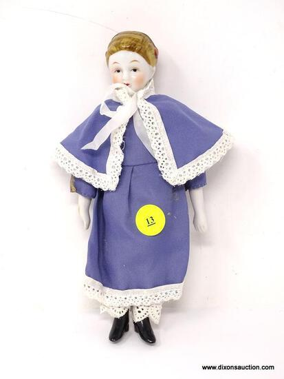 ANTIQUE PORCELAIN DOLL WITH A BLUE AND WHITE LACE DRESS. MEASURES APPROXIMATELY 8 IN TALL. ITEM IS