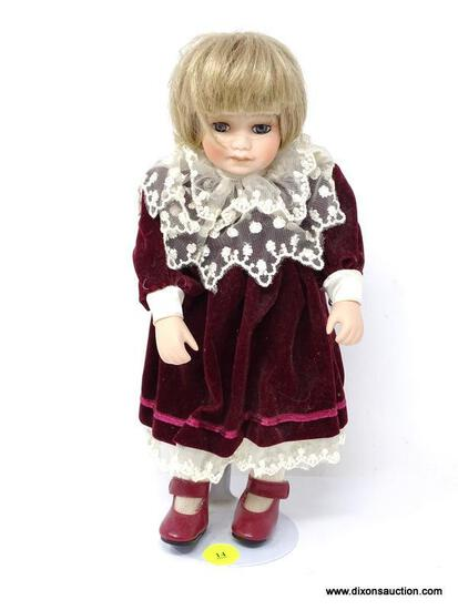 VINTAGE PORCELAIN DOLL IN A BURGUNDY DRESS WITH WHITE LACE ACCENTS. HAS STAND AND MEASURES 11 IN