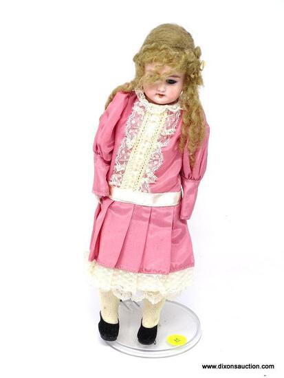 VINTAGE PORCELAIN DOLL IN A PINK DRESS WITH WHITE LACE ACCENTS. HAS STAND AND MEASURES 12 IN TALL.