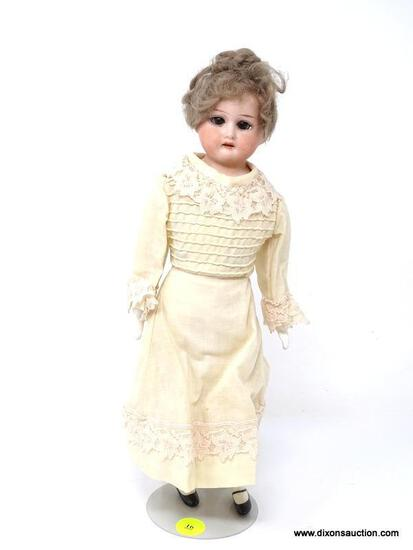 VINTAGE PORCELAIN DOLL IN AN OFF-WHITE DRESS WITH LACE ACCENTS. HAS STAND AND MEASURES 12.25 IN