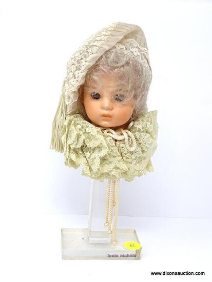 LOUIS NICHOLE PORCELAIN VICTORIAN DOLL HEAD MOUNTED ON LUCITE BASE. MEASURES 10.5 IN TALL. ITEM IS