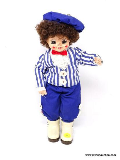 VINTAGE PORCELAIN DOLL OF A YOUNG BOY IN A BLUE AND WHITE STRIPED SHIRT WITH BLUE PANTS AND WHITE