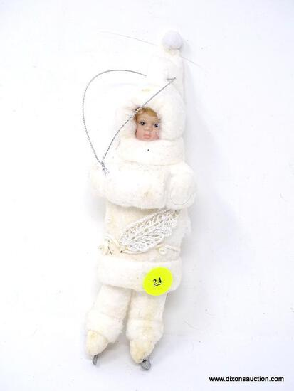 HANGING ORNAMENT OF A YOUNG ICE SKATER IN WHITE WITH HANDWARMER. MEASURES 8.5 IN TALL. ITEM IS SOLD