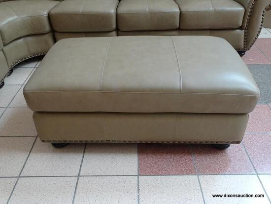 BRAND NEW TOP GRAIN LEATHER TAUPE OTTOMAN BY ABBYSON. HAS BRASS STUDDED ACCENTS ALONG THE EDGE AND