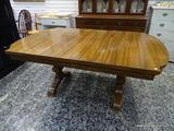 (R1) OAK DINING TABLE WITH TRESTLE AND STRETCHER BASE. INCLUDES ONE 9 IN LEAF. MEASURES 42 IN X 66