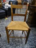 (R1) OAK MULE EARRED AND RUSH BOTTOM CHAIR. MEASURES 18 IN X 18 IN X 34 IN. ITEM IS SOLD AS IS WHERE