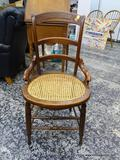 (R1) VICTORIAN WALNUT HIP REST SIDE CHAIR WITH CANE BOTTOM SEAT AND SPINDLE LEG SUPPORTS. MEASURES