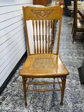 (R1) SOLID OAK SIDE CHAIR WITH CANE BOTTOM SEAT AND SPINDLE BACK. MEASURES 17 IN X 19 IN X 39 IN.
