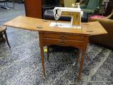 (R1) VINTAGE SINGER TOUCH & SEW SEWING MACHINE IN MAPLE CASE WITH TURNED LEGS. MEASURES 24 IN X 18.5