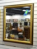 (R1) VINTAGE GOLD TONE AND BLACK FRAMED MIRROR WITH BEVELED GLASS EDGE. MEASURES 27 IN X 33 IN. ITEM