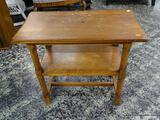 (R1) 2 TIER OAK END / SIDE TABLE WITH STRETCHER BASE. MEASURES 14 IN X 26 IN X 22 IN. ITEM IS SOLD