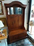 (R1) PINE HALL TREE WITH BRASS COAT HOOKS, A MIRRORED BACK CREST, AND A LIFT-TOP BENCH STYLE SEAT.