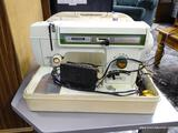 (R1) UNIVERSAL BRAND SEWING MACHINE WITH HARD VINYL CASE AND STRETCH STITCH TECHNOLOGY. ITEM IS SOLD