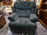 (R1) OVERSIZED GREEN UPHOLSTERED RECLINER WITH ROLLED ARMS. MEASURES 38 IN X 40 IN X 46 IN. ITEM IS