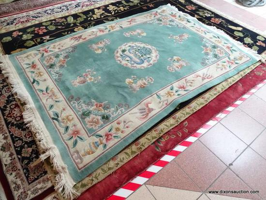 HANDMADE SCULPTED CHINESE RUG IN GREEN, IVORY, AND MAUVE WITH A DRAGON THEMED CENTER MEDALLION.