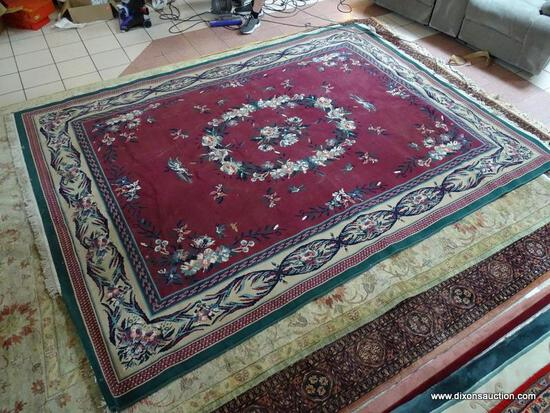 MACHINE MADE ORIENTAL STYLE RUG IN GREEN, IVORY, AND BURGUNDY. MEASURES APPROXIMATELY 7 FT 10 IN X