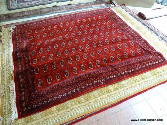 MACHINE MADE KARASTAN SILKY BOKHARA IN RED, IVORY AND BLUE. MEASURES APPROXIMATELY 8 FT X 10 FT.