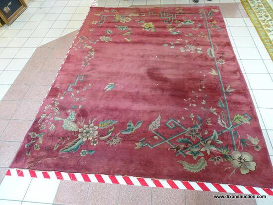 VINTAGE MACHINE MADE ORIENTAL RUG IN MAROON AND GREEN. SHOWS MOTH DAMAGE. MEASURES APPROXIMATELY 8