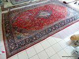 HANDMADE PERSIAN IN RED, BLUE, AND IVORY WITH LARGE CENTER MEDALLION. HAS DAMAGE. MEASURES