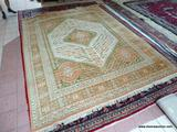 HANDMADE ORIENTAL RUG IN GREEN, ORANGE, AND IVORY. MEASURES APPROXIMATELY 8 FT 11 IN X 11 FT 9 IN.