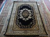MACHINE MADE ORIENTAL STYLE RUG IN BLACK, BEIGE, AND IVORY. MEASURES APPROXIMATELY 7 FT 2 IN X 5 FT