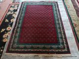 MACHINE MADE ORIENTAL STYLE IN BURGUNDY, GREEN, AND BEIGE. MEASURES APPROXIMATELY 5 FT 4 IN X 7 FT 8